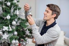 Hombre que mira Bell mientras que adorna la Navidad Fotografía de archivo libre de regalías