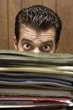 Hombre que mira con fijeza de detrás la pila de carpetas. Imagenes de archivo