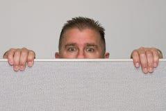 Hombre que mira con fijeza sobre cubículo de la oficina imagenes de archivo