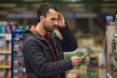 Hombre que mira confundido el teléfono móvil en supermercado Fotografía de archivo