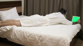 Hombre que mira datos sobre la tableta digital El hombre en hotel miente en cama y panel táctil con metrajes