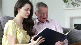 Hombre que mira el álbum de foto con la nieta adulta metrajes