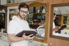 Hombre que mira el catálogo la tienda del baño Fotografía de archivo libre de regalías
