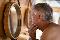 Hombre que mira el espejo en cabaña imágenes de archivo libres de regalías