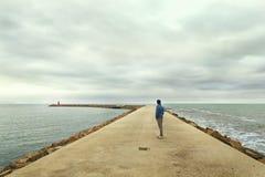 Hombre que mira el faro en paisaje marino Imágenes de archivo libres de regalías