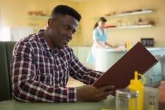 Hombre que mira el menú en restaurante Imagen de archivo