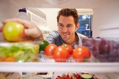 Hombre que mira el refrigerador interior por completo de la comida y que elige Apple Imagen de archivo libre de regalías