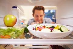 Hombre que mira el refrigerador interior por completo de la comida y que elige la ensalada Fotografía de archivo