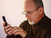 Hombre que mira el teléfono celular Imagen de archivo libre de regalías