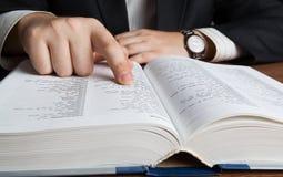 Hombre que mira en el diccionario grande Foto de archivo libre de regalías