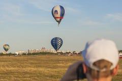 Hombre que mira en los Aire-globos que participan en taza internacional de la aerostática Foto de archivo libre de regalías