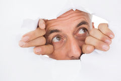 Hombre que mira a escondidas a través de superficie blanca rasgada Imagen de archivo
