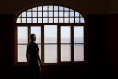 Hombre que mira fijamente hacia fuera una ventana sucia Fotos de archivo libres de regalías