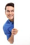 Hombre que mira furtivamente sobre el cartel en blanco Imágenes de archivo libres de regalías