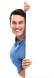 Hombre que mira furtivamente sobre el cartel en blanco Fotografía de archivo libre de regalías
