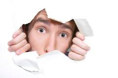 Hombre que mira furtivamente a través del agujero en el papel Imagen de archivo