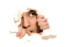 Hombre que mira furtivamente a través del agujero en el papel Foto de archivo