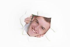 Hombre que mira furtivamente a través del agujero en papel Imagen de archivo libre de regalías