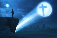Hombre que mira la cruz brillante al borde del acantilado Fotografía de archivo libre de regalías