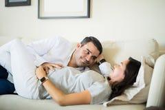 Hombre que mira a la esposa expectante que descansa sobre Sofa At Home foto de archivo