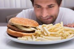 Hombre que mira la hamburguesa y las patatas fritas imágenes de archivo libres de regalías