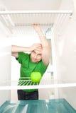 Hombre que mira la manzana en refrigerador Imagen de archivo libre de regalías