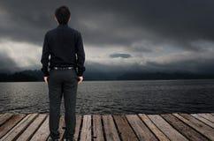 Hombre que mira la tormenta en la plataforma Imagen de archivo libre de regalías