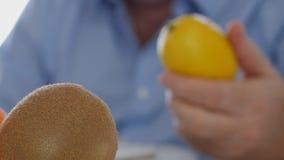 Hombre que mira a las frutas para guardar a disposición y para analizar un limón y una fruta de kiwi almacen de metraje de vídeo