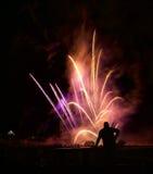 Hombre que mira los fuegos artificiales por la tarde del Año Nuevo Los fuegos artificiales agradables estallan Foto de archivo