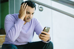 Hombre que mira malas noticias en el teléfono móvil imagen de archivo libre de regalías