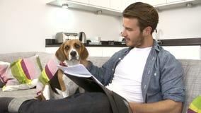Hombre que mira papeleo y que juega con el perro casero en casa metrajes