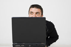 Hombre que mira para arriba detrás de la computadora portátil Fotos de archivo libres de regalías