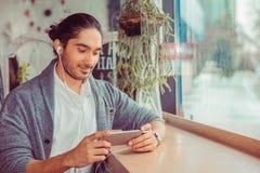 Hombre que mira para llamar por teléfono, el mandar un SMS, enviando SMS foto de archivo