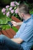 Hombre que mira smartphone Fotos de archivo