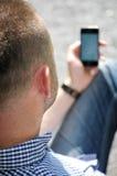Hombre que mira smartphone Fotografía de archivo
