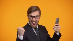 Hombre que mira smartphone y que hace sí la muestra, condiciones de crédito favorables, apostando metrajes