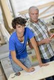 Hombre que mira sobre un trabajador más joven del hombro Fotos de archivo