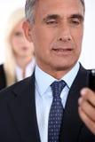 Hombre que mira su teléfono móvil Fotografía de archivo libre de regalías