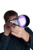 Hombre que mira a través de un telescopio Imagen de archivo libre de regalías