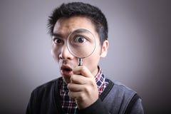 Hombre que mira a través de una lupa imagen de archivo