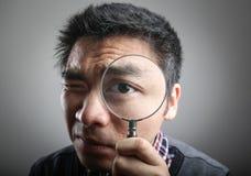 Hombre que mira a través de una lupa imagen de archivo libre de regalías