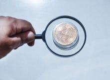 Hombre que mira a través de una lupa en bitcoin imagenes de archivo