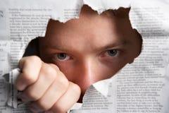 Hombre que mira a través del agujero en periódico Foto de archivo