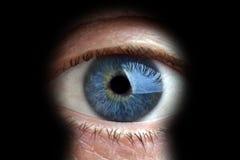 Hombre que mira a través del ojo de la cerradura