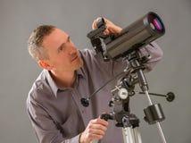 Hombre que mira a través del telescopio Imagenes de archivo