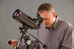 Hombre que mira a través del telescopio Imágenes de archivo libres de regalías