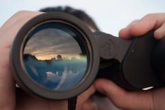 Hombre que mira a través de los prismáticos Foto de archivo libre de regalías