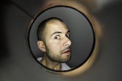 Hombre que mira un agujero Imagenes de archivo