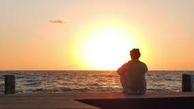 Hombre que mira un amanecer al final del día almacen de video