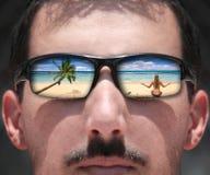 Hombre que mira a una mujer en la playa con Sungla Imagen de archivo libre de regalías